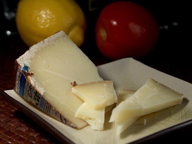 fromage avec un citron et tomate en arrière plan